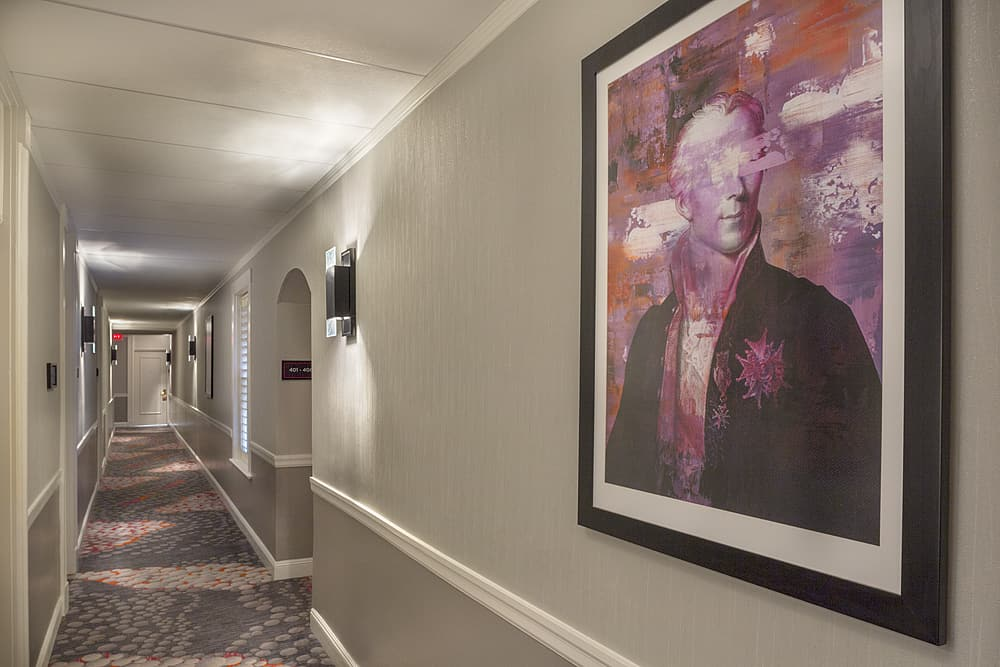 Hallway with painting of historical figure and patterned carpet.
