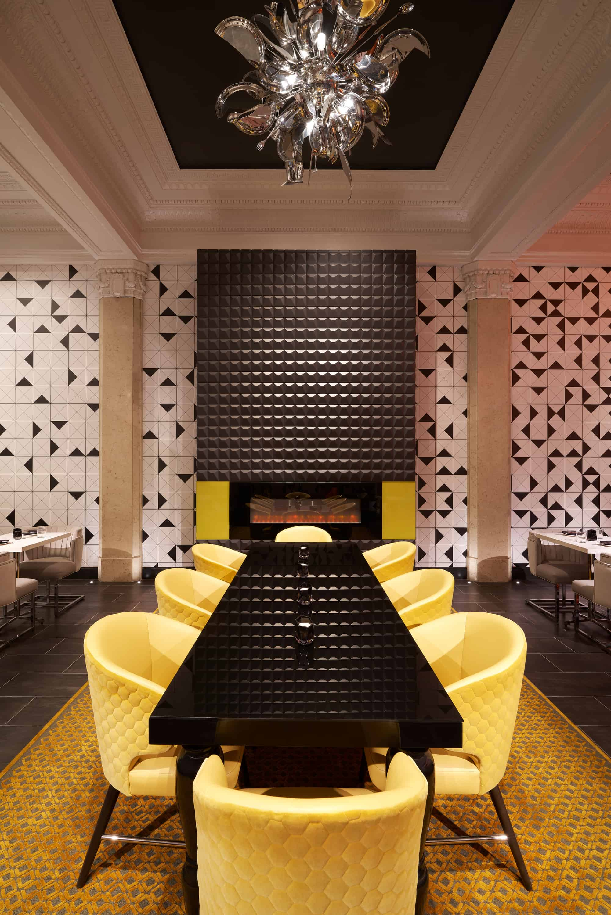 Lobby lounge with yellow chairs, white and black patterned walls and fireplace