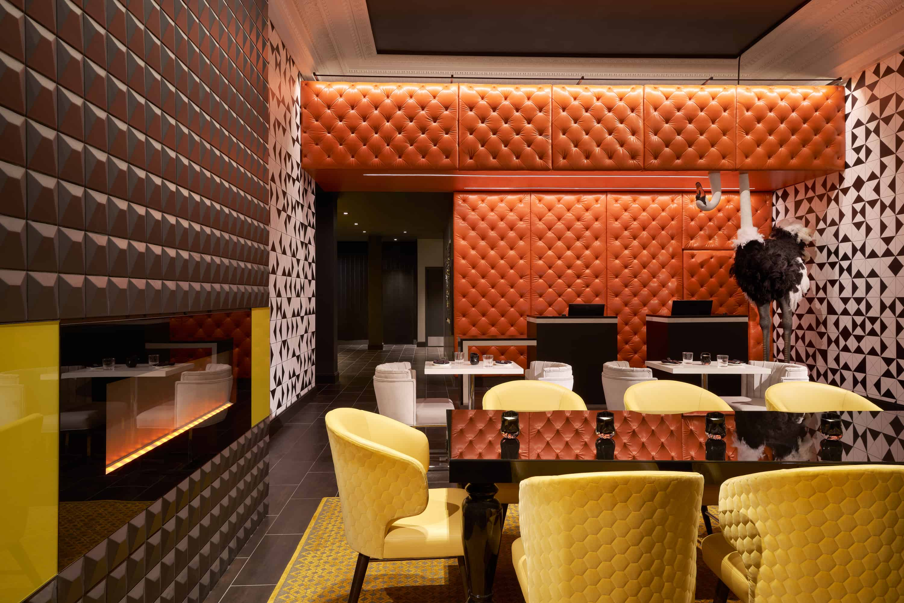 Lobby lounge with yellow chairs, white and black patterned walls and fireplace.