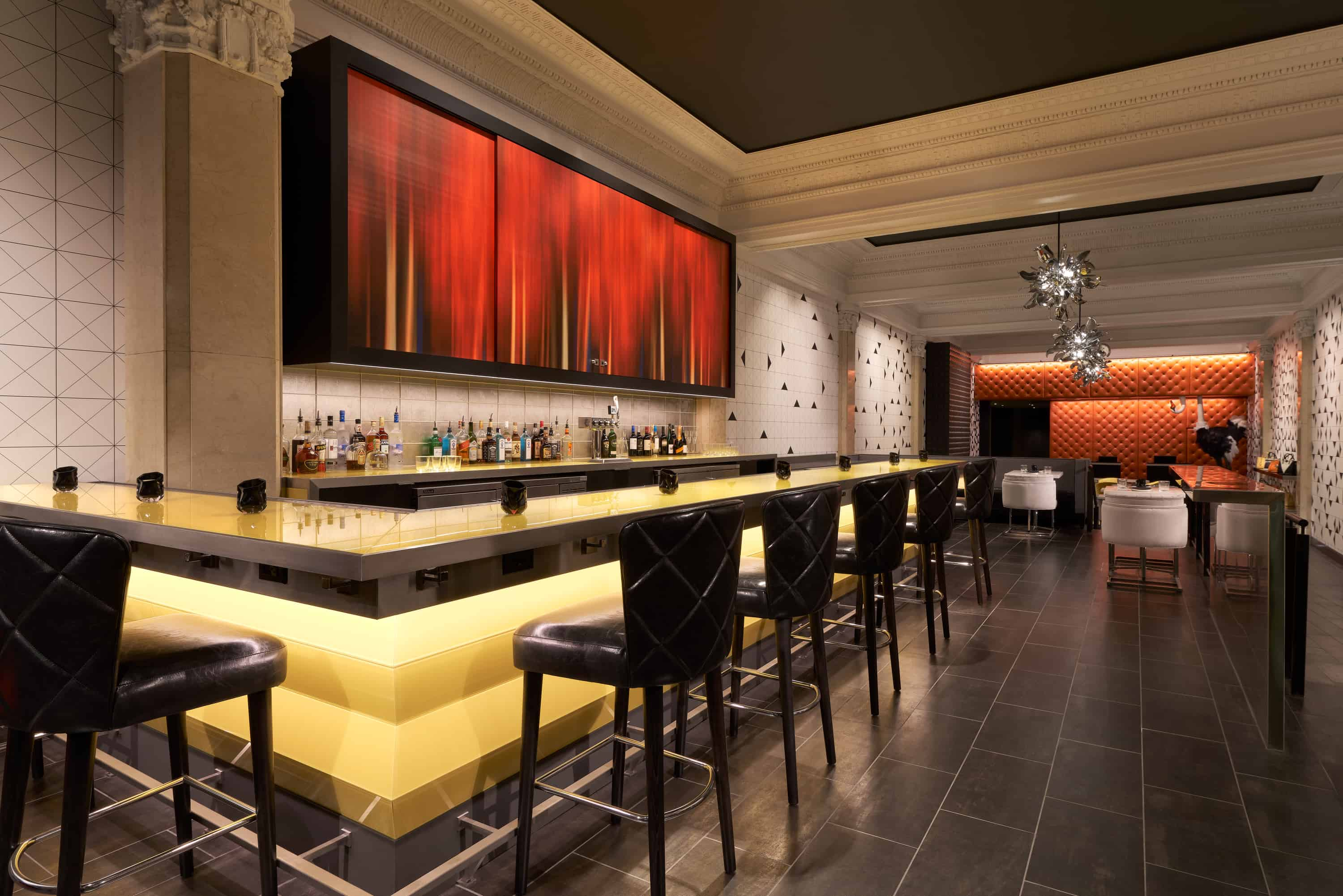 Struzzo bar with painted cabinets, yellow underlit bar and black tufted leather chairs.