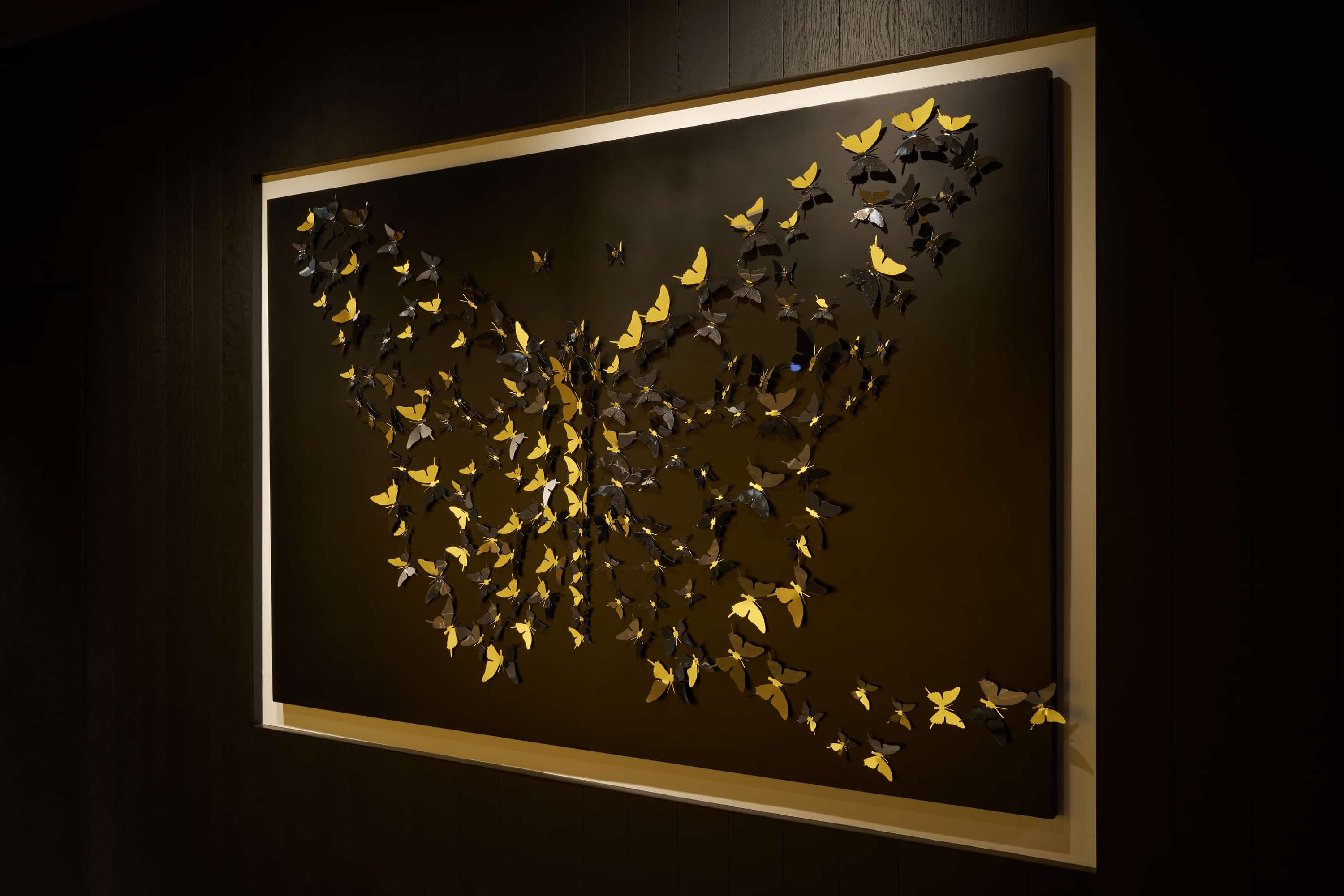 Butterfly wall art composed of smaller gold butterflies.