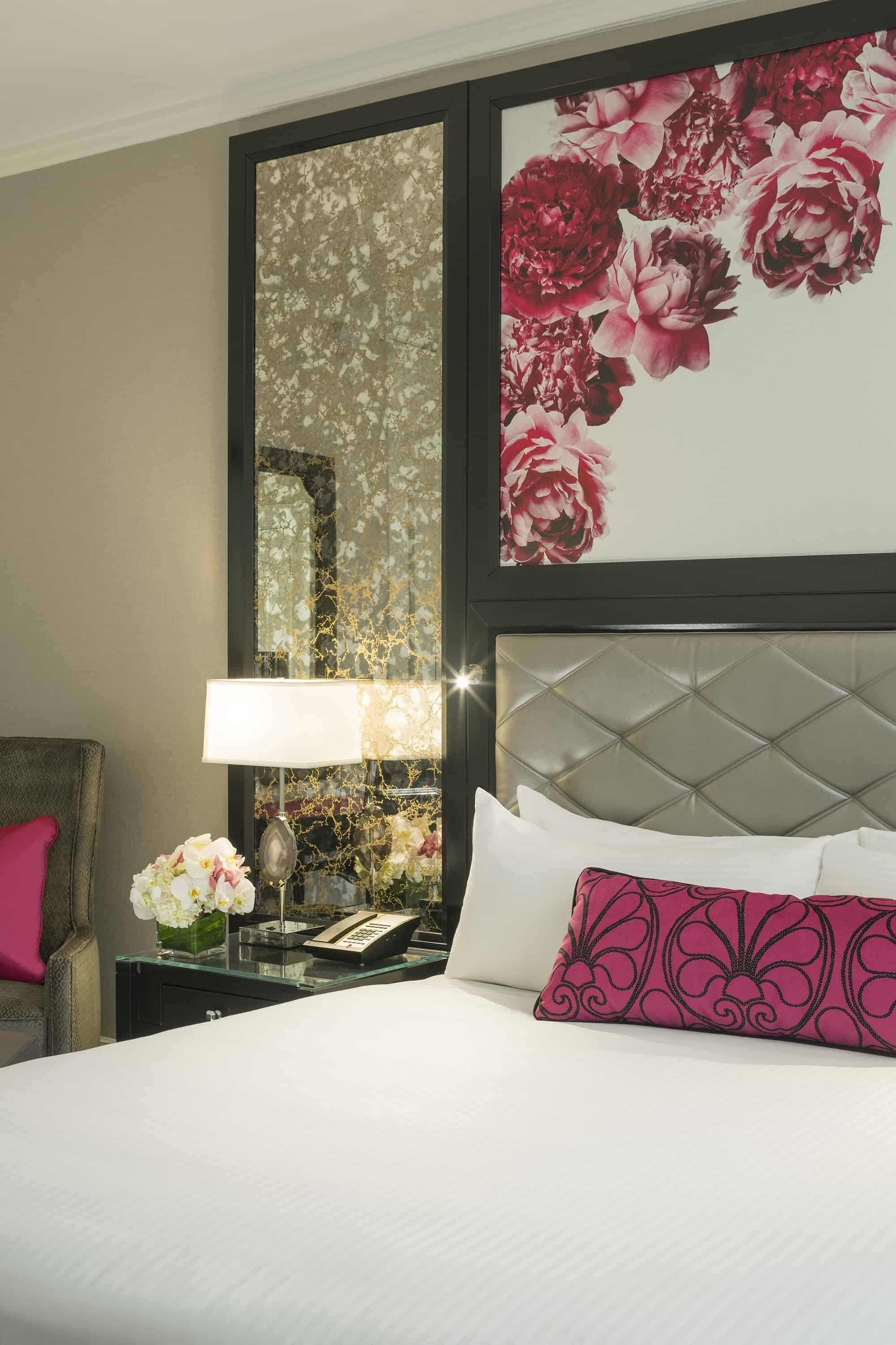 King room bed detail with peony painting and mercury glass side panels.