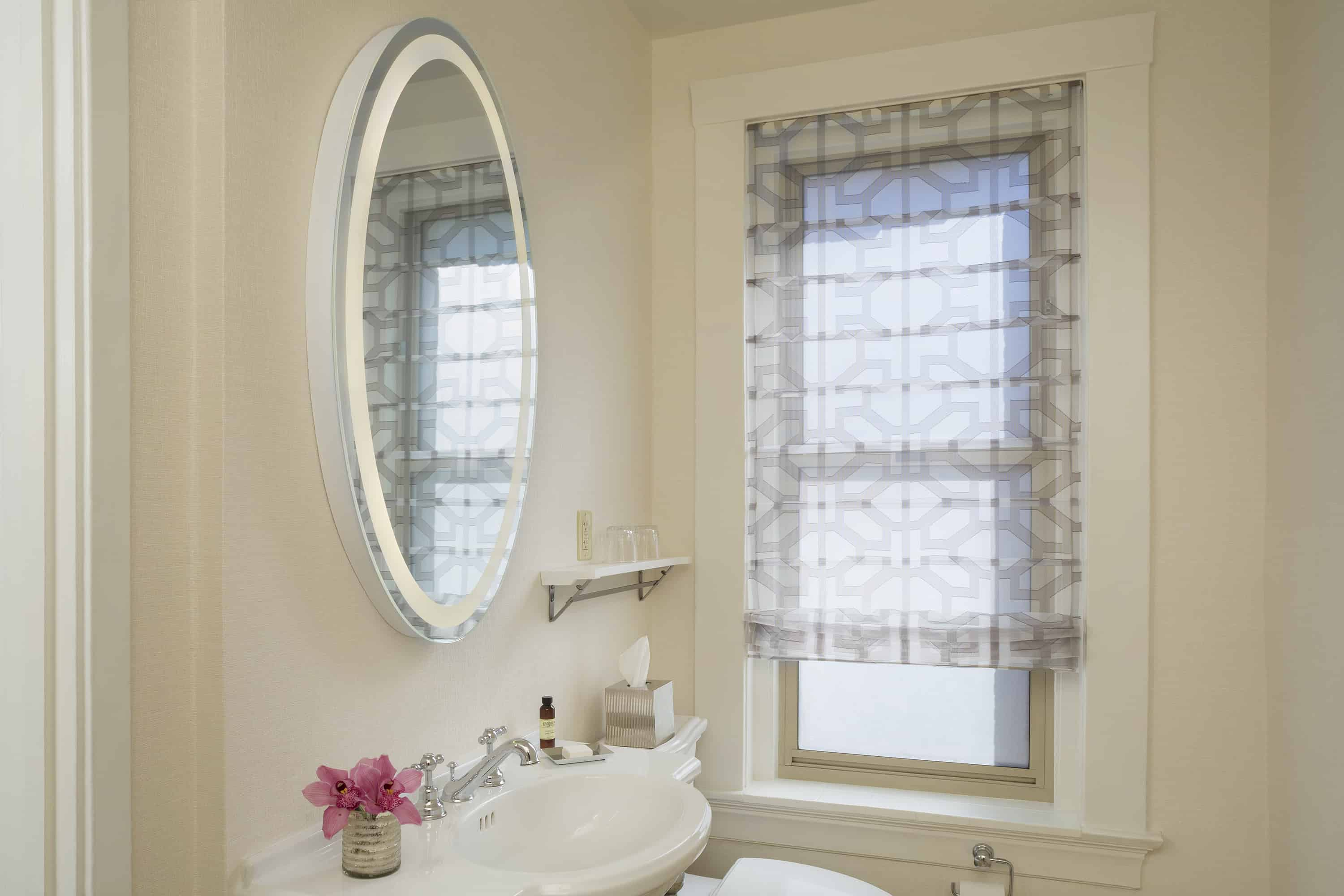 Guest room bathroom detail with lighted mirror and window.